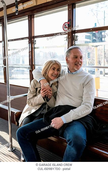 Senior couple riding on tram in city