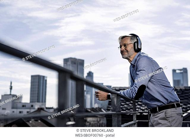 Grey-haired man with headphones enjoying city view