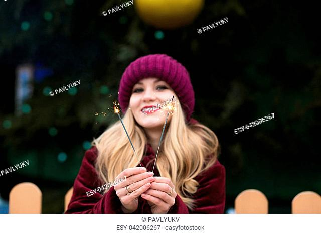 Emotional young woman holding glowing Bengal lights at the main Christmas tree in Kyiv. Blur effect