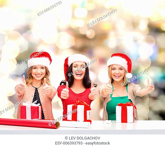 christmas, holidays, gesture, decoration and people concept - smiling women in santa helper hats with decorating paper and gift boxes showing thumbs up over...