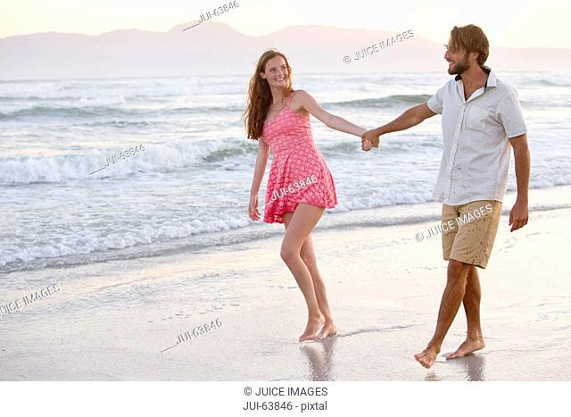 Couple, holding hands, walking on sunny beach