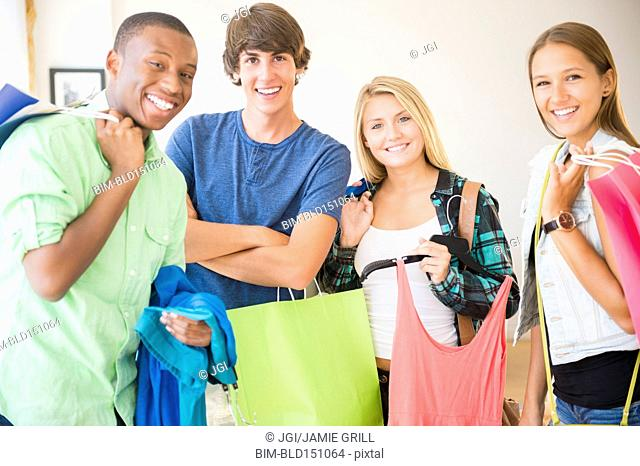 Smiling teenagers holding shopping bags