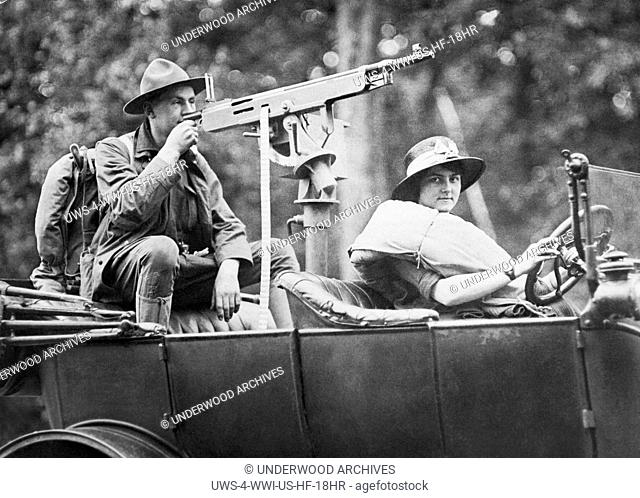 New York: July 13, 1917.A couple has mounted a machine gun on their car and touring to show people how such a Home Defense Measure can be done if it becomes...