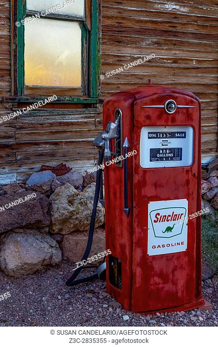 Sinclair Gas Pump - Red vintage Sinclair Gasoline Pump still stands by an old wooden structure with the setting sun reflected in the window