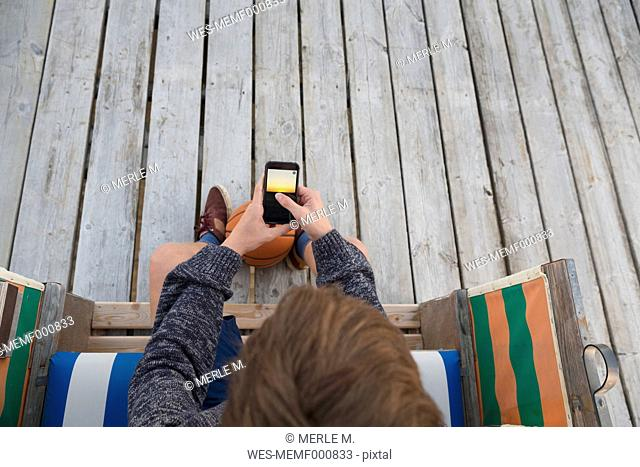 Teenage boy with basketball and smartphone sitting in hooded beach chair
