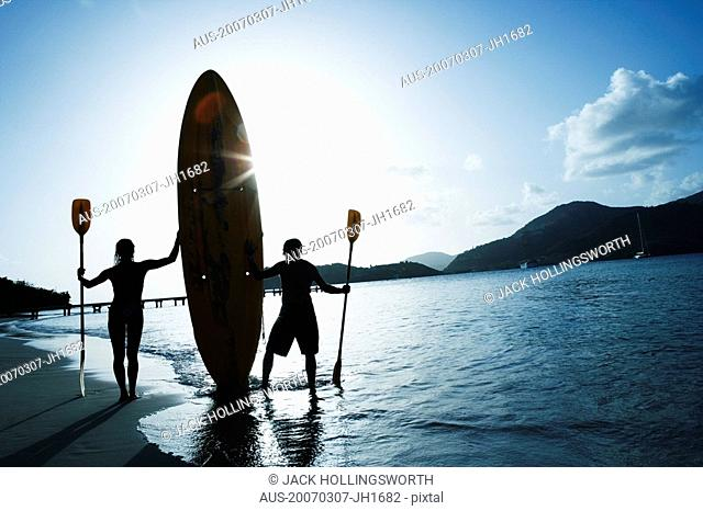Silhouette of a man and a woman holding oars and a surfboard on the beach