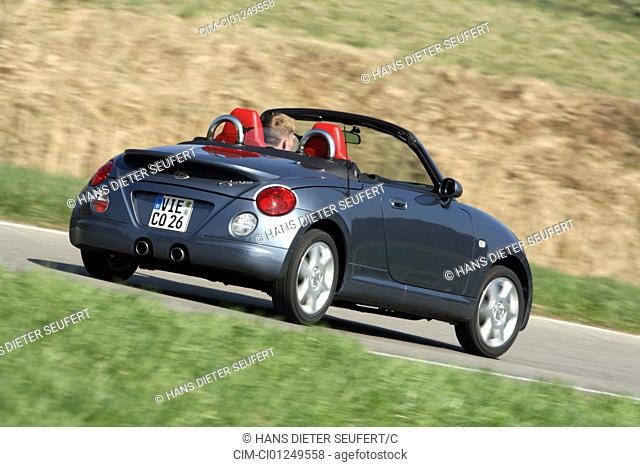 Daihatsu Copen, model year 2006-, anthracite, driving, diagonal from the back, rear view, country road, open top
