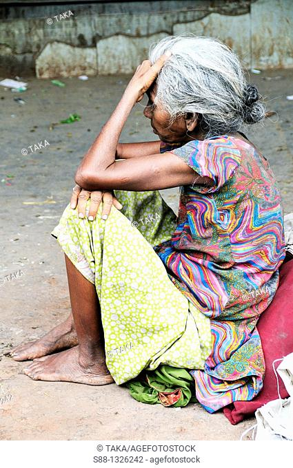 Woman sitting on the road who need help, Delhi India