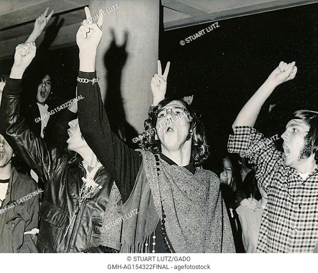 Students wearing hippie attire, including one student with long hair and a poncho, hold their fingers aloft in a peace sign gesture