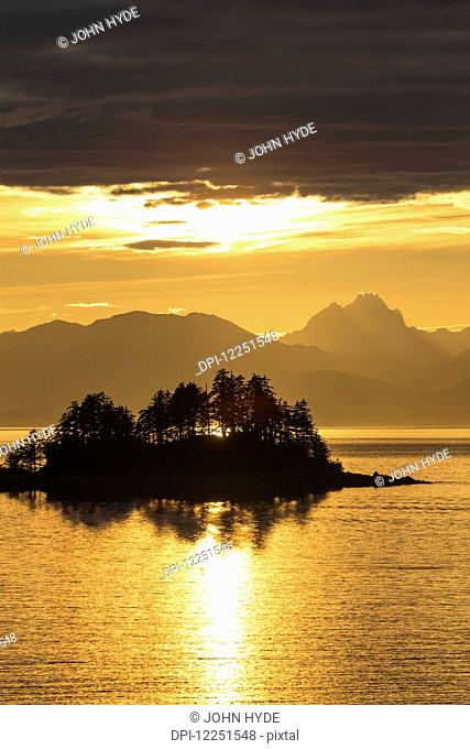A summer sunset colours the sky adjacent to Lynn Canal, with Chilkat Mountains in the distance; Alaska, United States of America