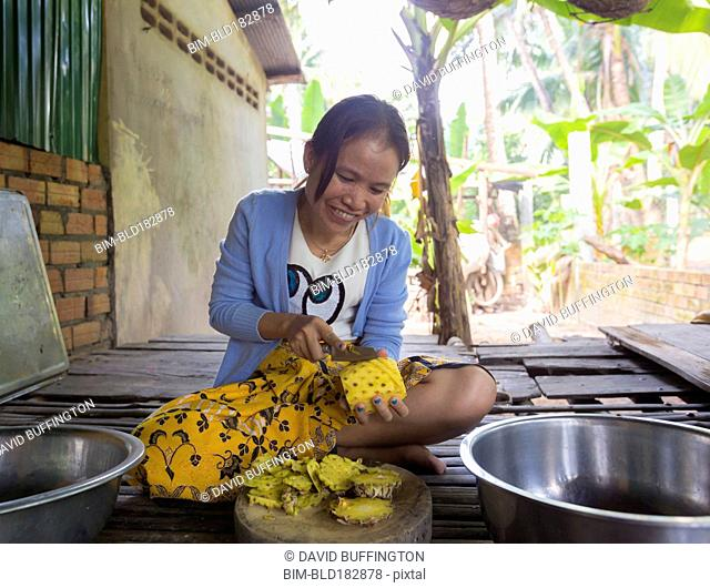 Asian woman peeling pineapple on patio