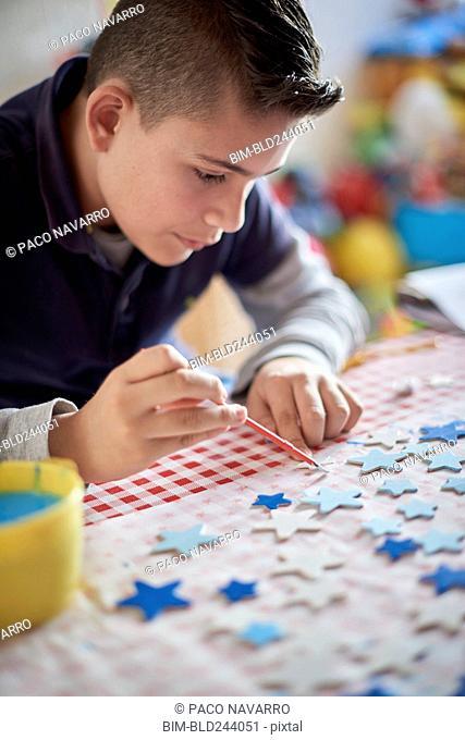 Hispanic boy painting stars at table