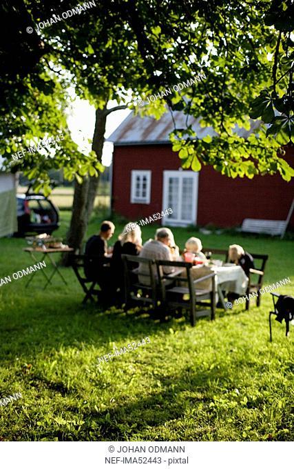 A family having dinner in the garden, Gotland, Sweden