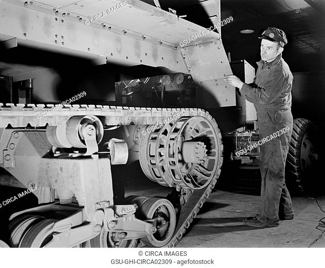 Worker Lowering Partly-finished Halftrac Scout Car Body on Chassis at War Plant that Formerly Produced Locks and Safes, Diebold Safe and Lock Company, Canton
