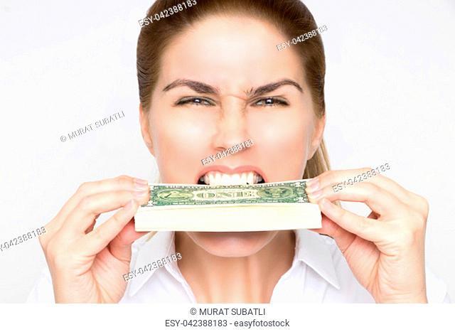 Gorgeous woman bites on a bundle of 100 Dollar bills