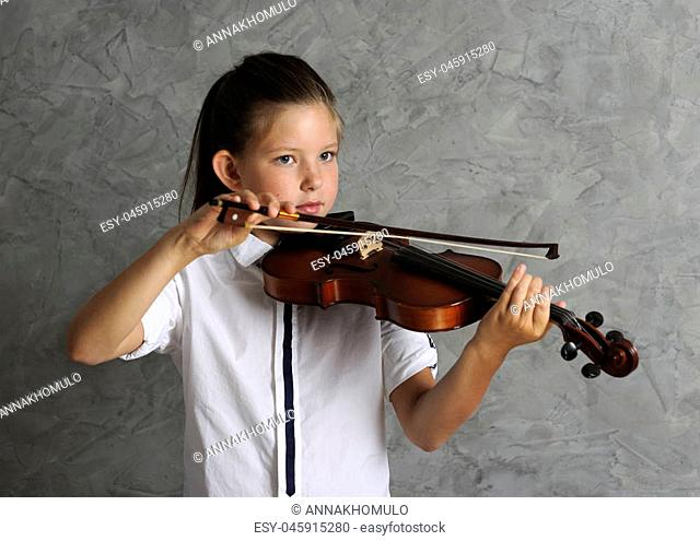 pretty girl playing violin on grey background