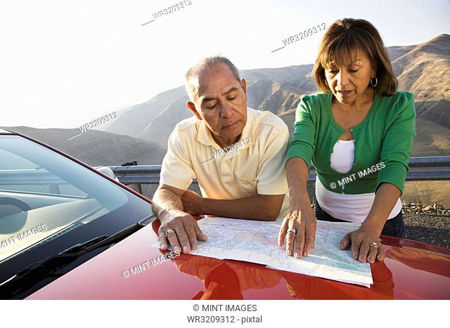 An Hispanic senior couple checking a paper map while pulled over at rest stop on a road trip