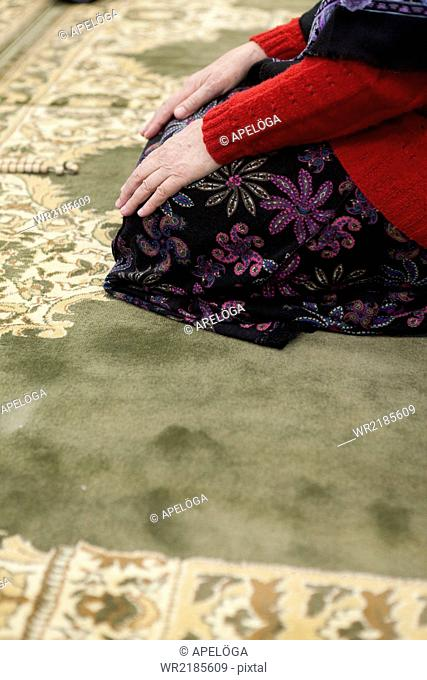 Cropped image of woman praying in mosque