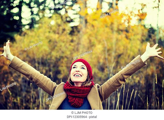 A beautiful young woman raising her hands in joy during an outing in a park in autumn; Edmonton, Alberta, Canada