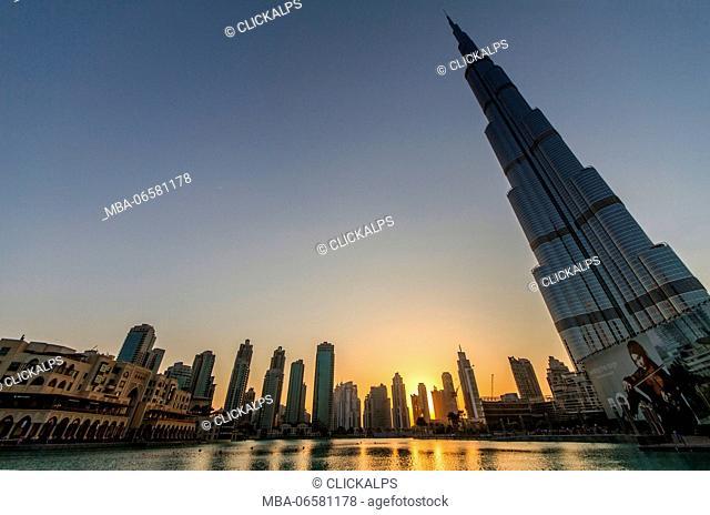 The Burj Khalifa skyscraper, its lake and the skyline of Dubai at the sunset, United Arab Emirates