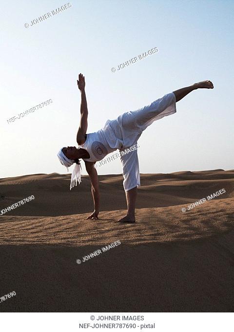 Woman performing yoga in the desert, Tunisia