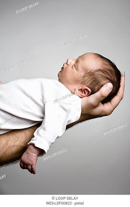 Father holding baby girl 0-4 weeks, side view, portrait