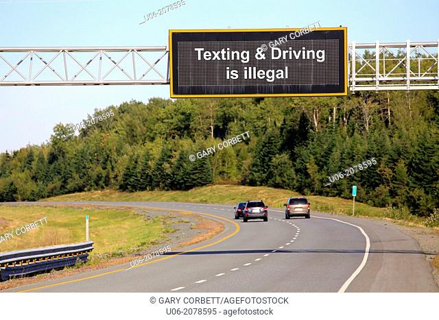 A highway sign that says Texting And Driving Is Illegal showing cars driving by it