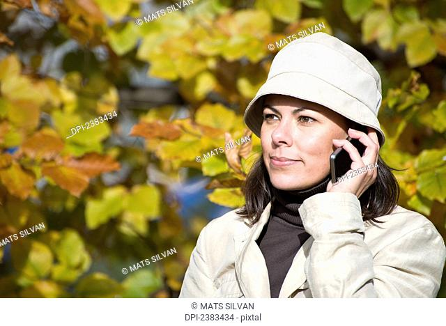 A woman talks on her cell phone with autumn colours on the trees; Locarno, Ticino, Switzerland
