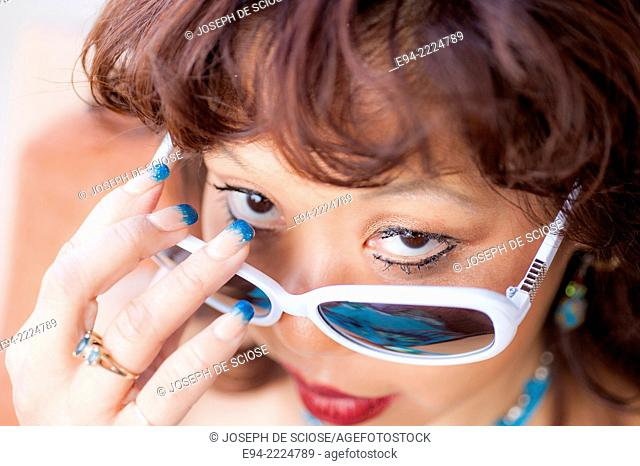 Close up portrait of a 38 year old Asian-American woman wearing white rimmed sunglasses, Looking over the farms at the camera