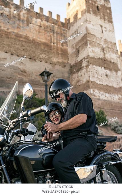 Spain, Banos de la Encina, mature couple with motorcycle with a sidecar looking at camera