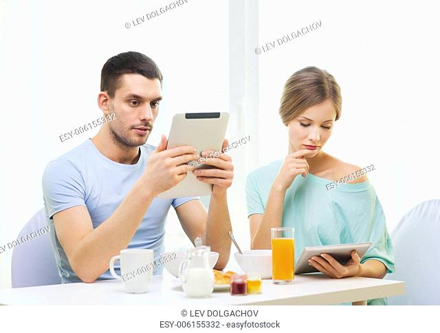 food, home, couple and technology concept - concentrated couple with tablet pc reading news and having breakfast at home