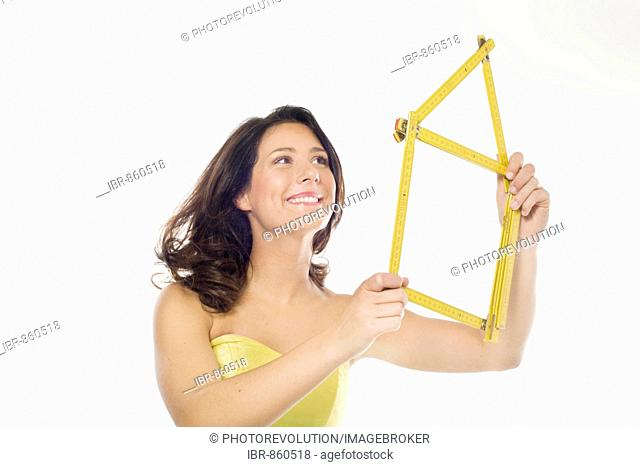 Young woman, wearing a yellow dress, smiling while holding in her hands a yellow folding ruler folded in the shape of a house