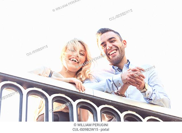 Portrait of young couple looking down from bridge