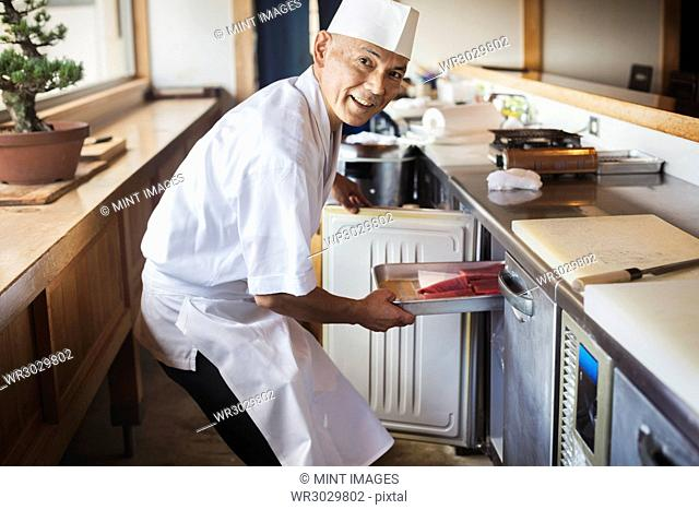 Chef working at a counter at a Japanese sushi restaurant, putting metal tray with fish in refrigerator