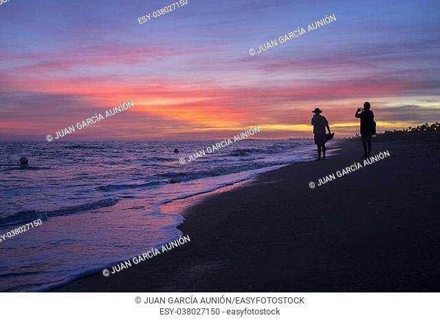 Elder tourist couple taking pictures at Islantilla beach during the magnificent sunrise. Huelva, Spain