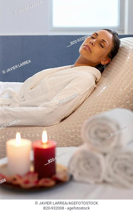Woman relaxing on hot stone seat, Spa-relais