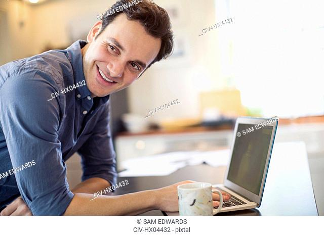 Smiling, confident man working at laptop in kitchen