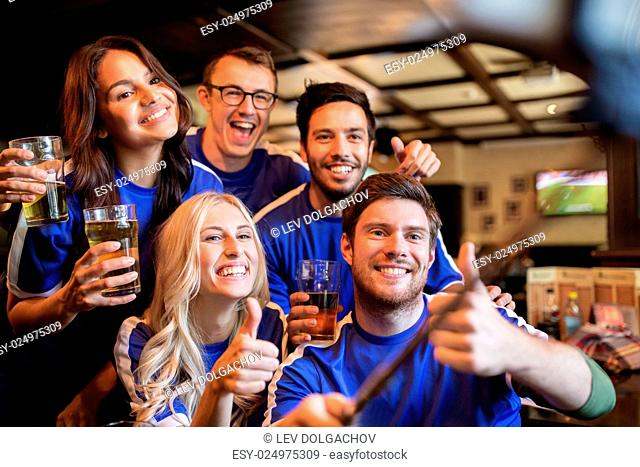 people, leisure, friendship and technology concept - happy friends or football fans taking picture by smartphone selfie stick
