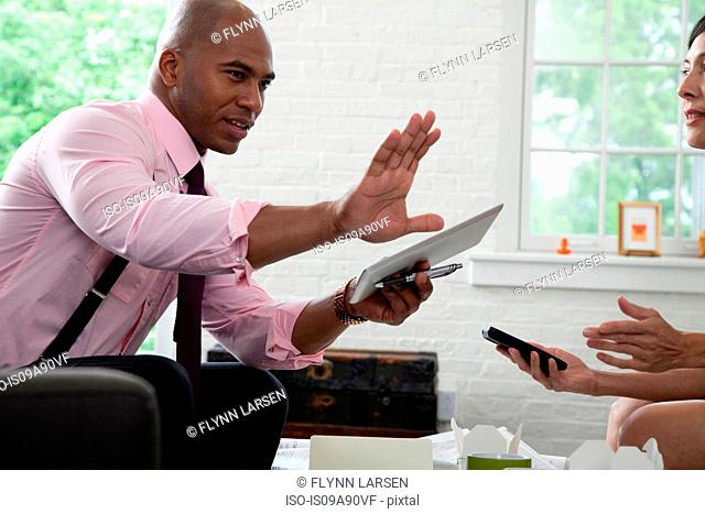 Mid adult office worker holding digital tablet and gesturing in meeting