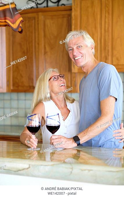 Happy husband and wife enjoying retirement in their kitchen while having red wine