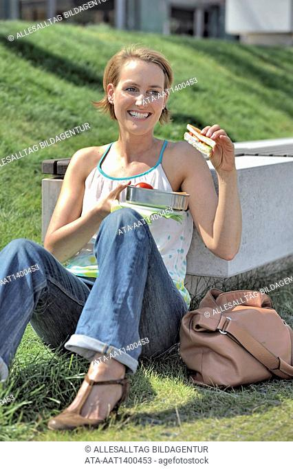 Woman sitting outside with her lunch box