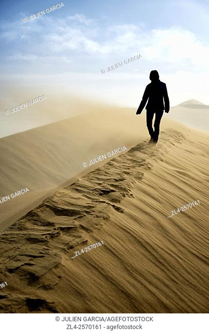 China, Gansu Province, Dunhuang, Crescent Lake (Yueyaquan), woman in the desert walking on the crest of a frozen sand dune, Model Released