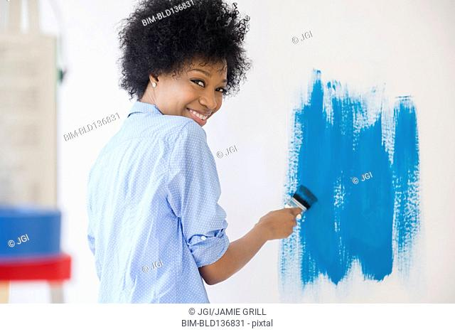 African American woman painting wall