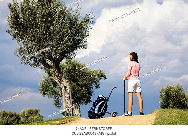 Female golfer with golf bag on course