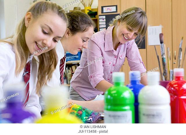 Art teacher teaching middle school students painting in art class