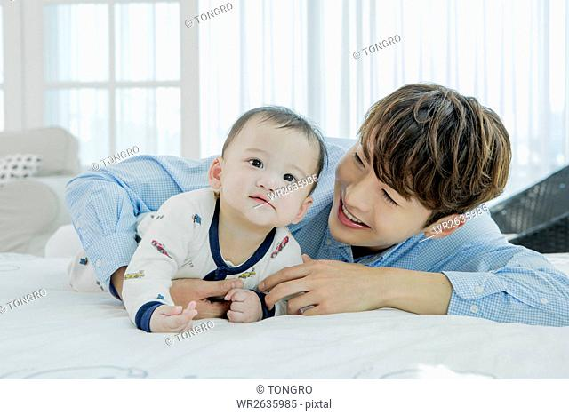 Portrait of loving father playing with his baby