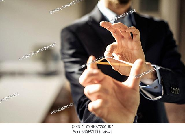 Hands of businessman aiming with rubber band and folded paper at viewer