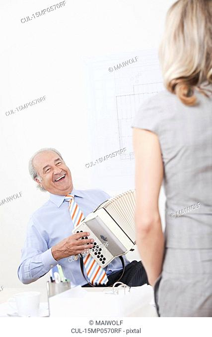 Man playing melodeon in an office