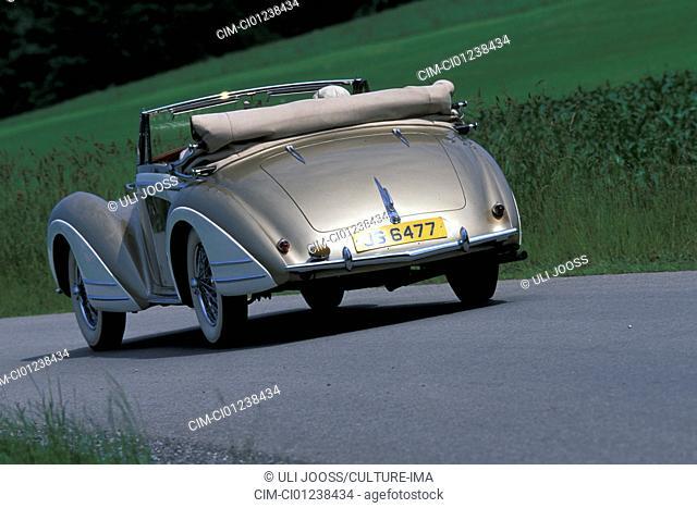 Car, Delahaye 135 M Henri Chapron, model year 1948, vintage car, convertible, convertible top, open, 1940s, fourties, driving, diagonal back, back view, road