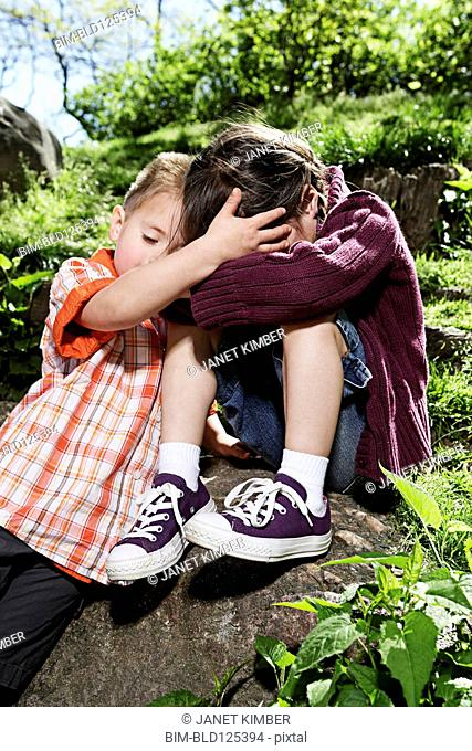 Mixed race boy comforting sister in park